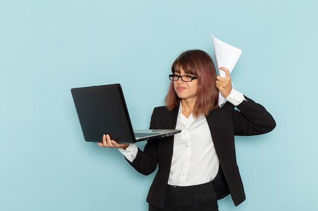 Vue de face femme employé de bureau tenant papier et ordinateur portable sur la surface bleue