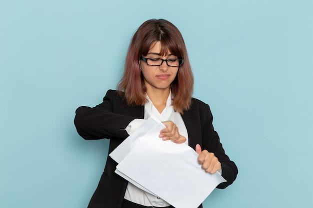 Vue de face femme employée de bureau en costume strict arnaquer des documents sur la surface bleue