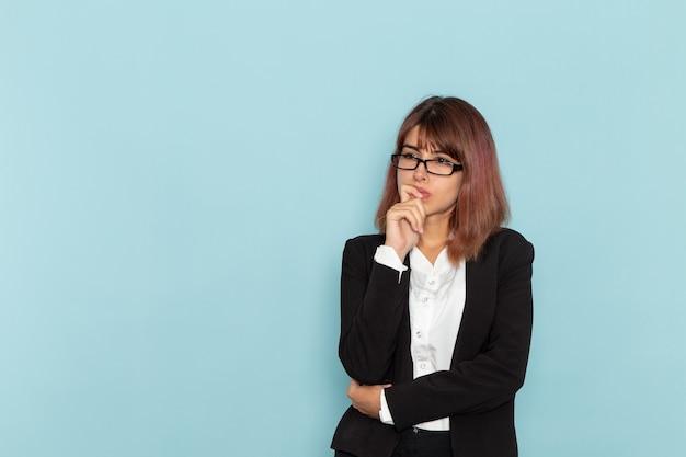 Vue de face femme employée de bureau en costume strict pensant sur la surface bleue