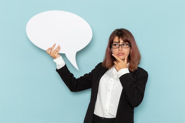 Vue de face femme employée de bureau tenant un énorme panneau blanc et pensant sur la surface bleue