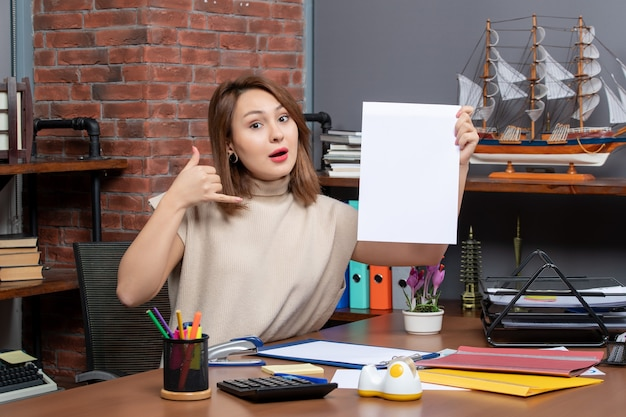 Vue de face d'une femme étonnée faisant appel moi signe de téléphone assis au bureau