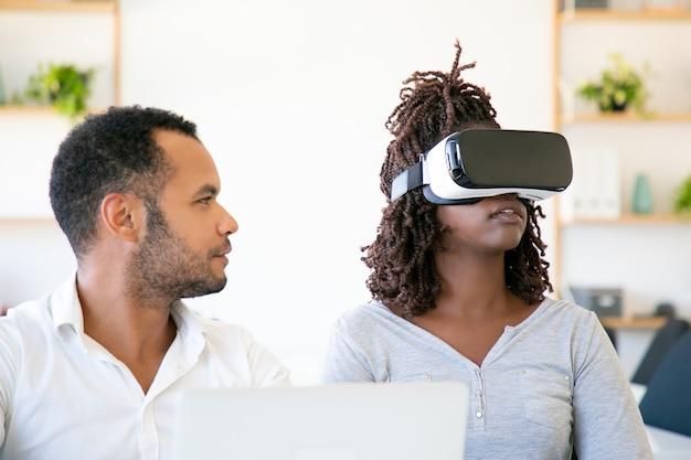 Vue de face d'une femme excitée testant un casque vr avec un assistant