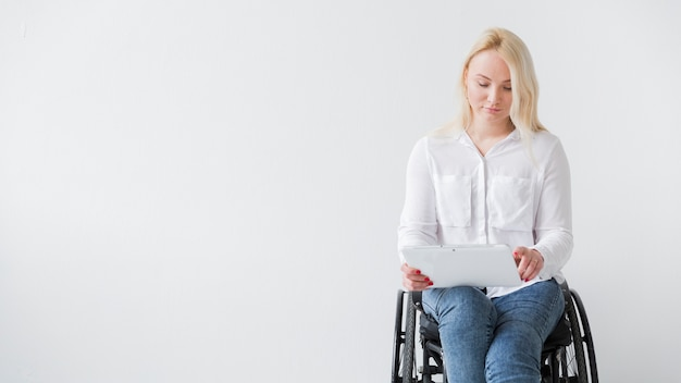 Vue de face de femme en fauteuil roulant travaillant sur tablette