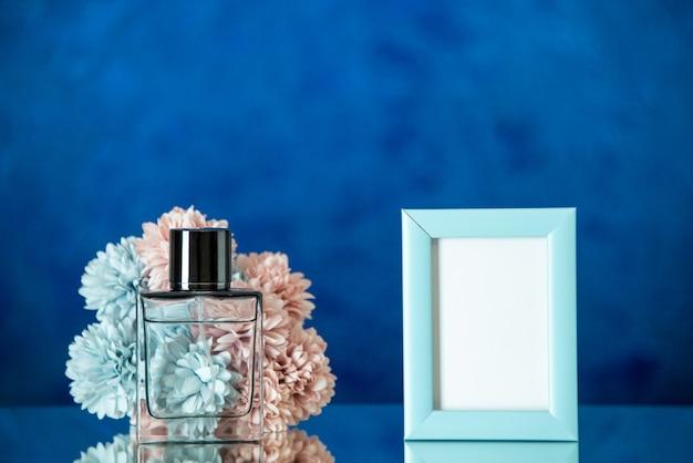 Vue de face femme flacon de parfum petit cadre photo bleu fleurs sur fond bleu foncé espace libre