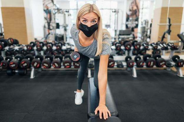 Vue de face de la femme avec une formation de masque médical au gymnase