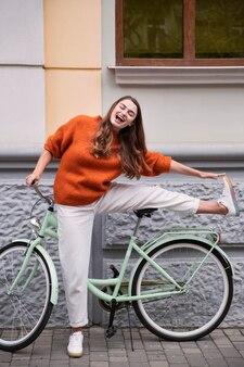Vue de face d'une femme heureuse posant avec son vélo à l'extérieur