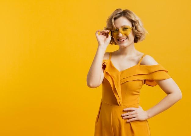 Vue de face de femme heureuse posant tout en portant des lunettes de soleil