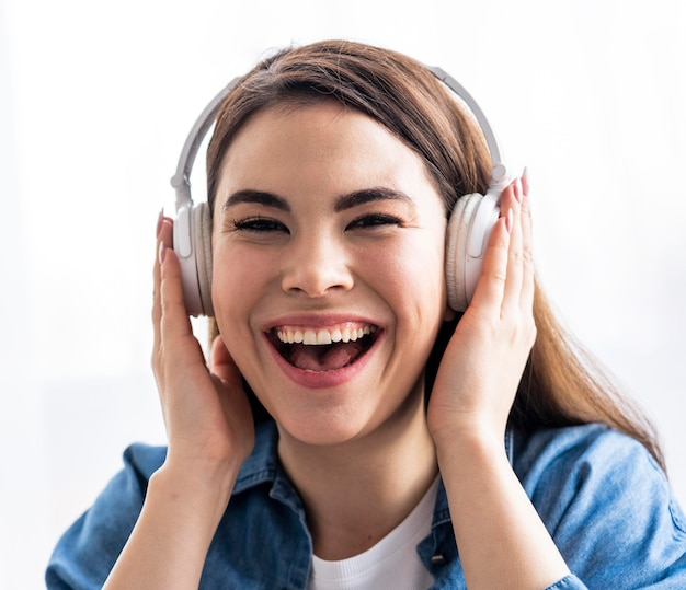 Vue de face d'une femme heureuse en riant et en écoutant de la musique sur des écouteurs