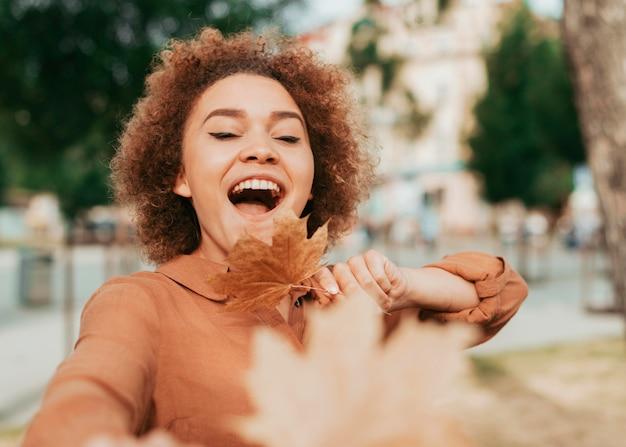Vue de face femme heureuse tenant une feuille sèche