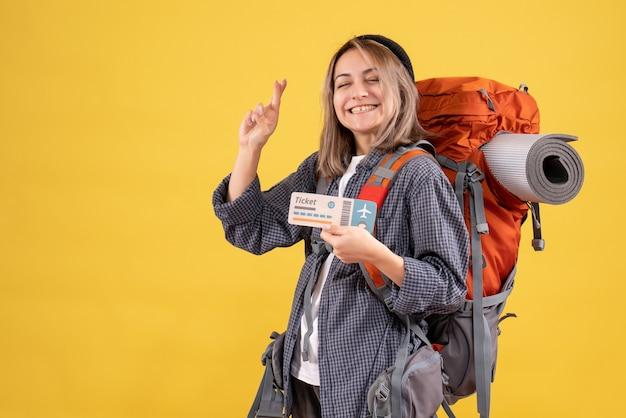 Vue de face de la femme heureuse de voyageur avec sac à dos tenant le signe de souhait de geste de signe