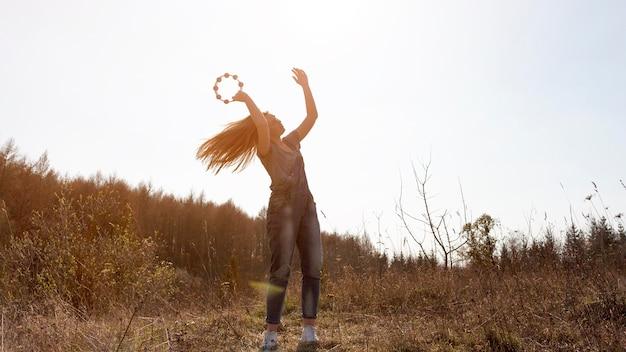Vue de face de femme insouciante jouant du tambourin dans la nature