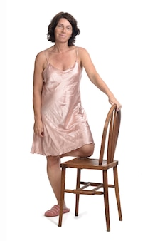 Vue de face d'une femme jouant avec une chaise avec chemise de nuit sur fond blanc,