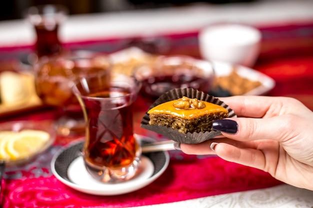 Vue de face femme mangeant un baklava azerbaïdjanais traditionnel avec du thé