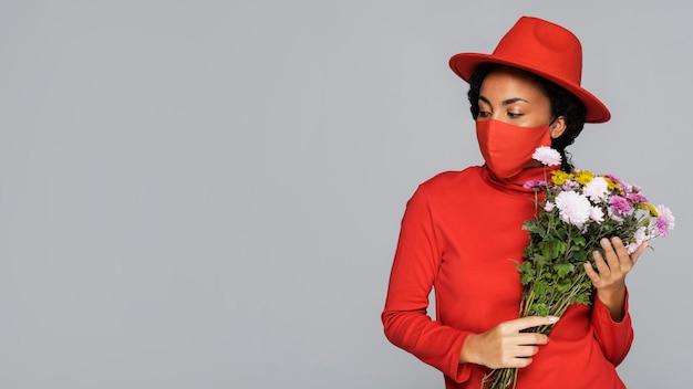 Vue de face de la femme avec masque et bouquet de fleurs