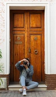 Vue de face de la femme avec un masque facial à l'extérieur, prendre des photos avec appareil photo