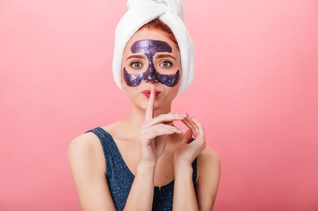 Vue de face de la femme avec un masque facial montrant le signe de silence. photo de studio de jeune femme en serviette posant sur fond rose pendant le traitement de la peau.