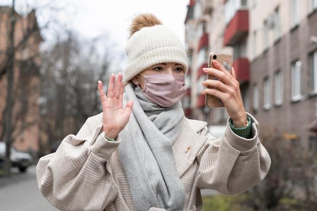 Vue de face de la femme avec un masque médical en agitant au smartphone