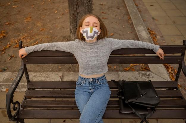 Vue de face femme avec masque médical assis sur un banc