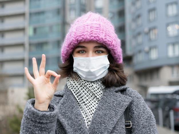 Vue de face de la femme avec un masque médical dans la ville montrant le signe correct