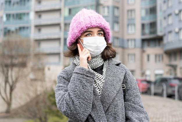Vue de face de la femme avec un masque médical dans la ville, parler sur smartphone