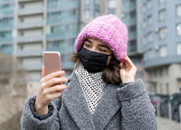 Vue de face de la femme avec un masque médical dans la ville prenant selfie