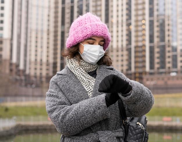 Vue de face de la femme avec un masque médical dans la ville en regardant la montre