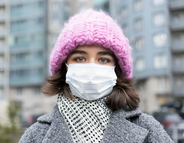 Vue de face de la femme avec un masque médical dans la ville