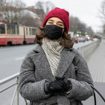 Vue de face de la femme avec un masque médical à l'extérieur dans la ville