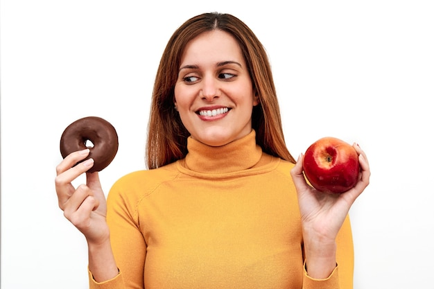 Vue de face d'une femme méconnaissable doutant de ce qu'il faut manger avec un beignet dans une main et une pomme dans l'autre.