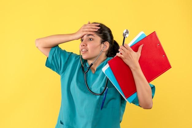 Vue de face femme médecin agitée avec des documents tenant sa tête sur fond jaune