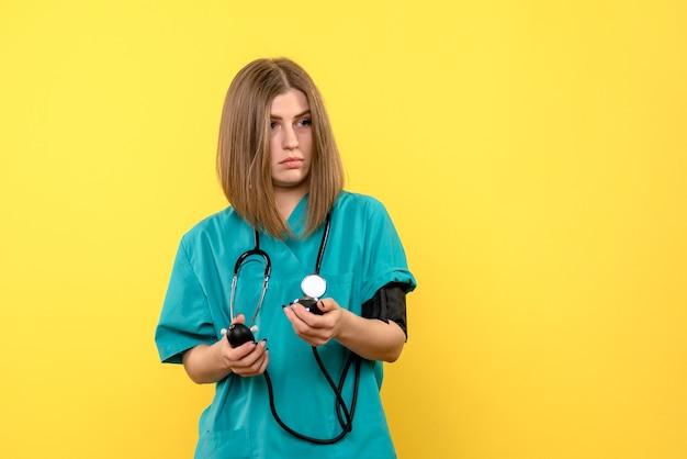 Vue de face femme médecin à l'aide de tonomètre sur l'espace jaune