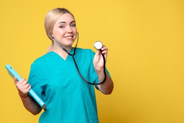 Vue de face de la femme médecin avec analyse et stéthoscope sur mur jaune