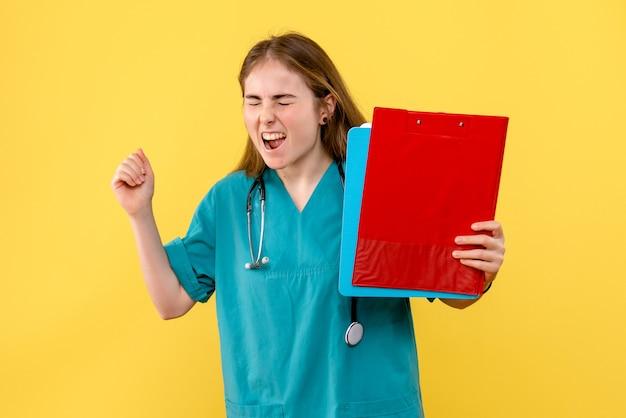 Vue de face femme médecin avec analyses sur fond jaune virus de l'hôpital de l'infirmière de la santé