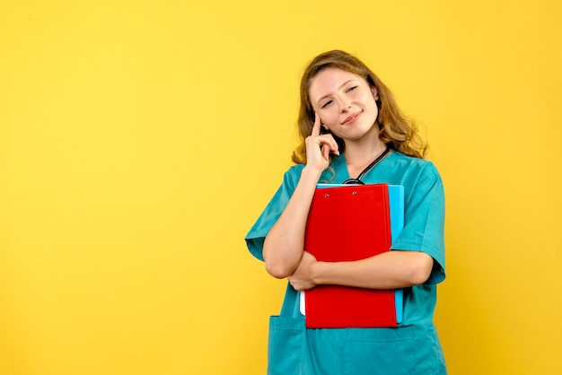 Vue de face de la femme médecin avec analyses sur mur jaune