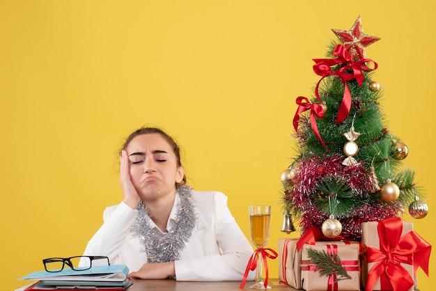 Vue de face femme médecin assis autour de cadeaux de noël et arbre triste sur fond jaune