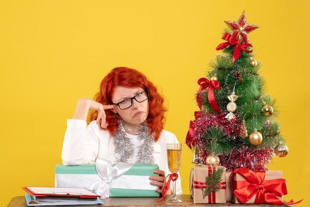 Vue de face femme médecin assis avec des cadeaux de noël et arbre sur un bureau jaune