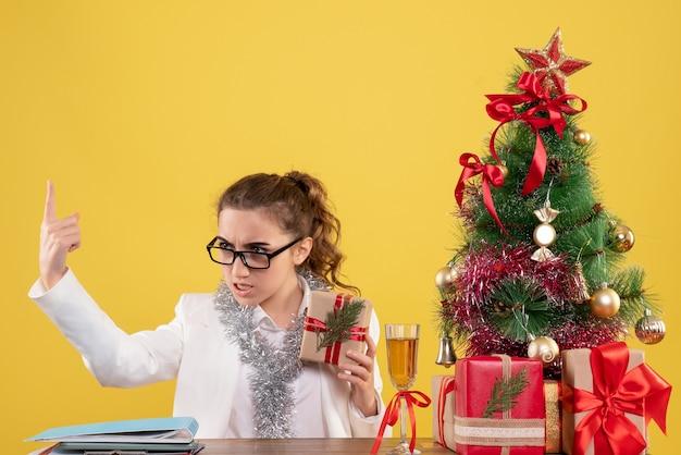 Vue de face femme médecin assis avec des cadeaux de noël et arbre sur fond jaune