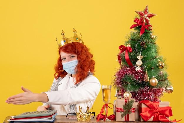 Vue de face femme médecin assis avec des cadeaux de noël et portant une couronne sur un bureau jaune