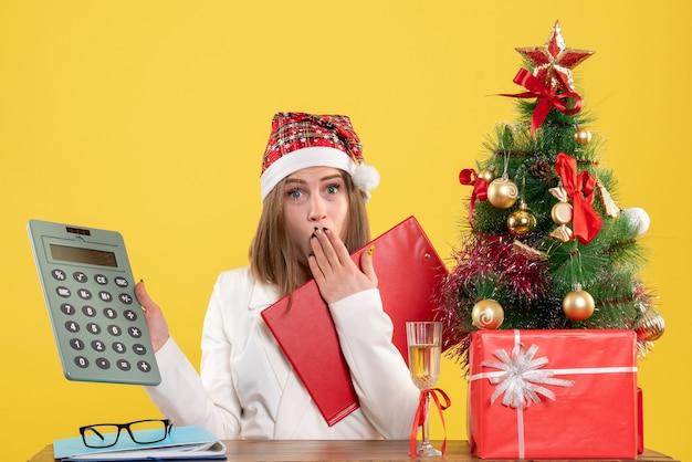 Vue de face femme médecin assis avec des cadeaux de noël tenant calculatrice sur un bureau jaune