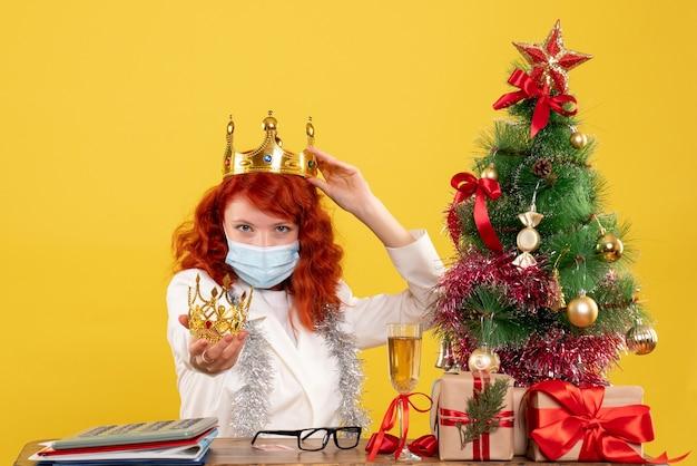Vue de face femme médecin assis avec des cadeaux de noël et tenant la couronne sur un bureau jaune