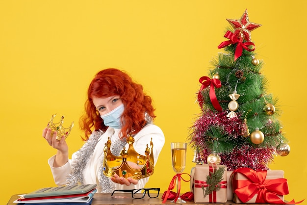 Vue de face femme médecin assis avec des cadeaux de noël et tenant des couronnes sur fond jaune