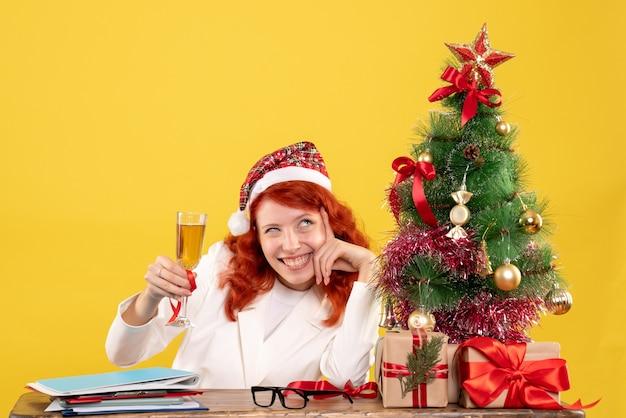Vue de face femme médecin assis et célébrant noël avec champagne