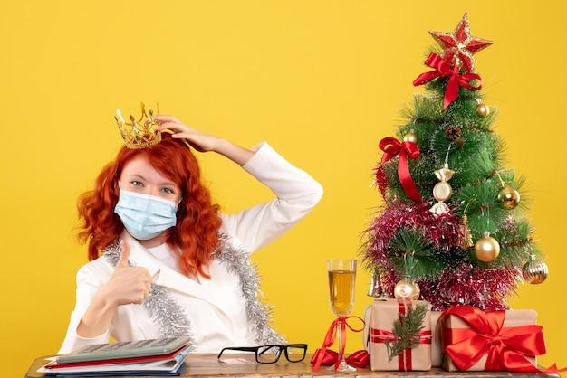 Vue de face femme médecin assis dans un masque avec des cadeaux de noël portant couronne sur fond jaune