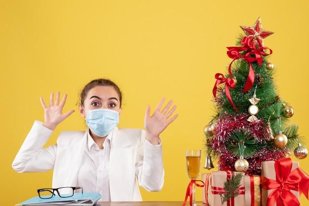 Vue de face femme médecin assis dans un masque de protection sur fond jaune avec arbre de noël et coffrets cadeaux