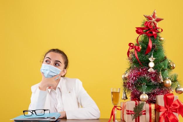 Vue de face femme médecin assis dans un masque de protection pensant sur fond jaune avec arbre de noël et coffrets cadeaux