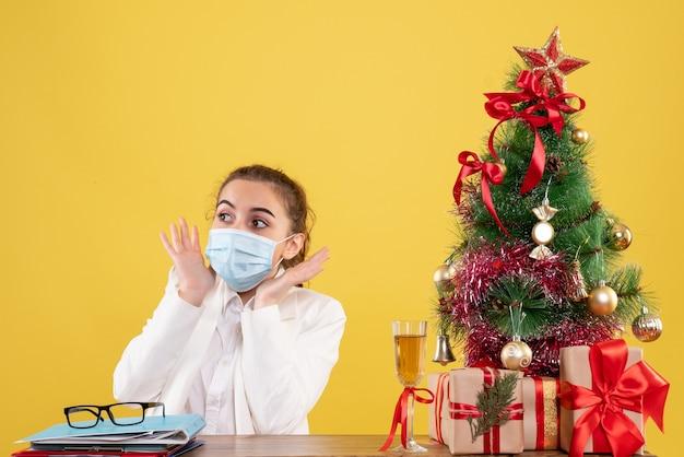 Vue de face femme médecin assis dans un masque de protection peur sur fond jaune avec arbre de noël et coffrets cadeaux