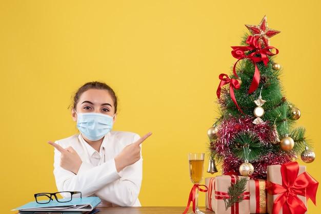 Vue de face femme médecin assis dans un masque de protection souriant sur fond jaune avec arbre de noël et coffrets cadeaux