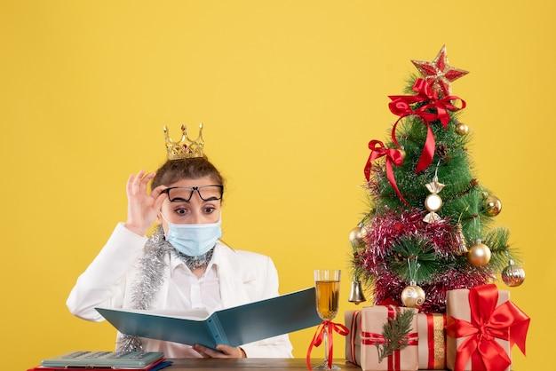 Vue de face femme médecin assis dans un masque stérile avec des documents sur fond jaune avec arbre de noël et coffrets cadeaux