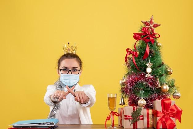 Vue de face femme médecin assis dans un masque stérile sur fond jaune avec arbre de noël et coffrets cadeaux