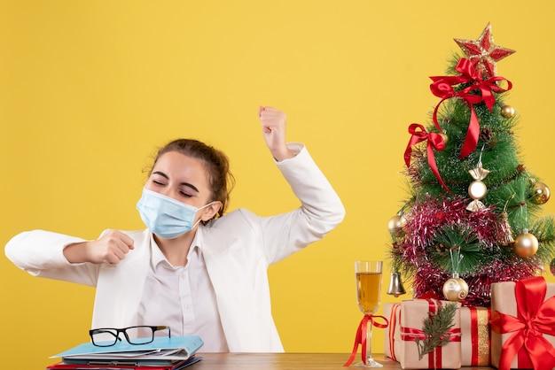 Vue de face femme médecin assis dans un masque stérile se réjouissant sur fond jaune avec arbre de noël et coffrets cadeaux